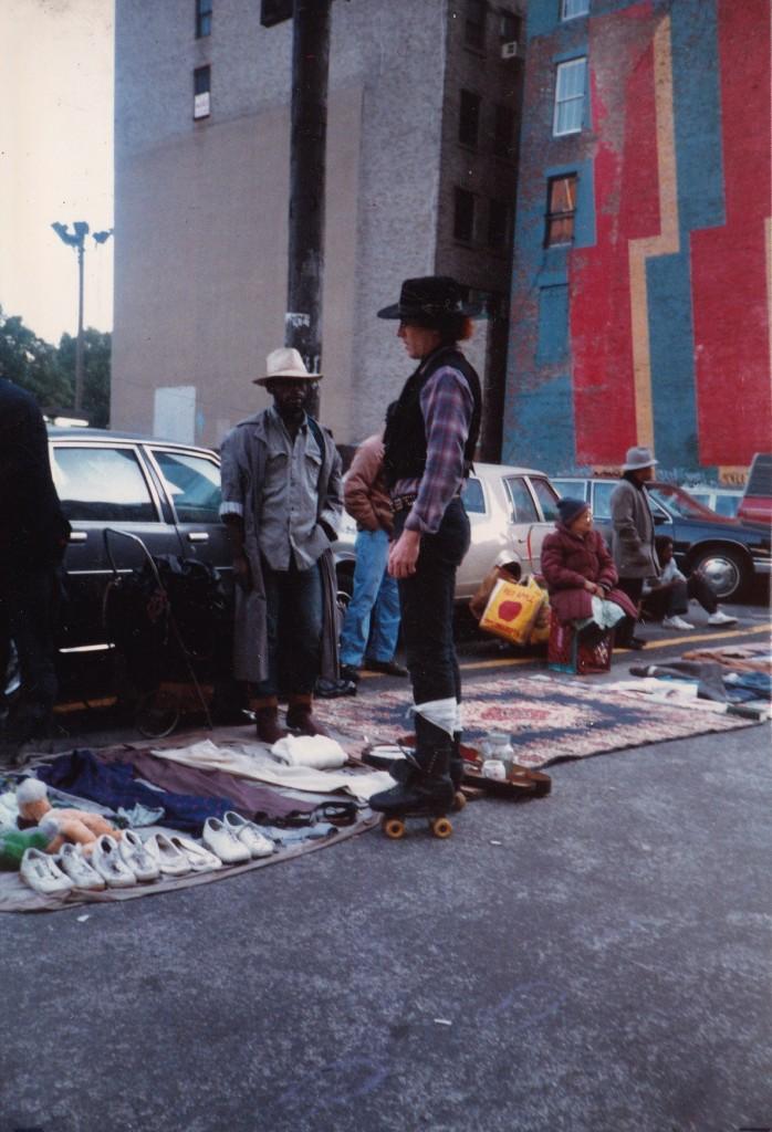 WHEEL THING...a cowboy on roller-skates speaks to people selling their belongings on street