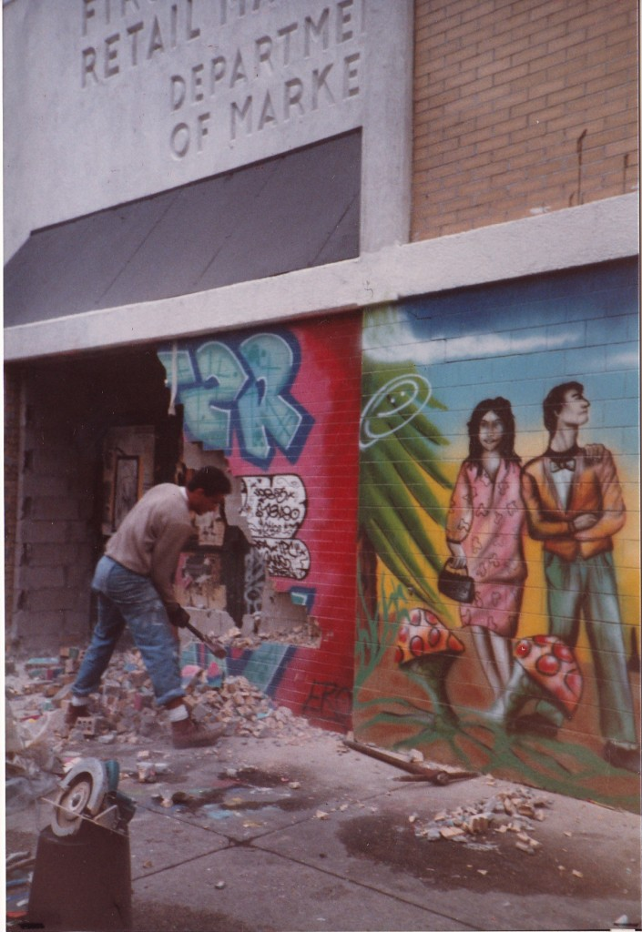 GOING DOWN...man demolishes a wall covered in street art