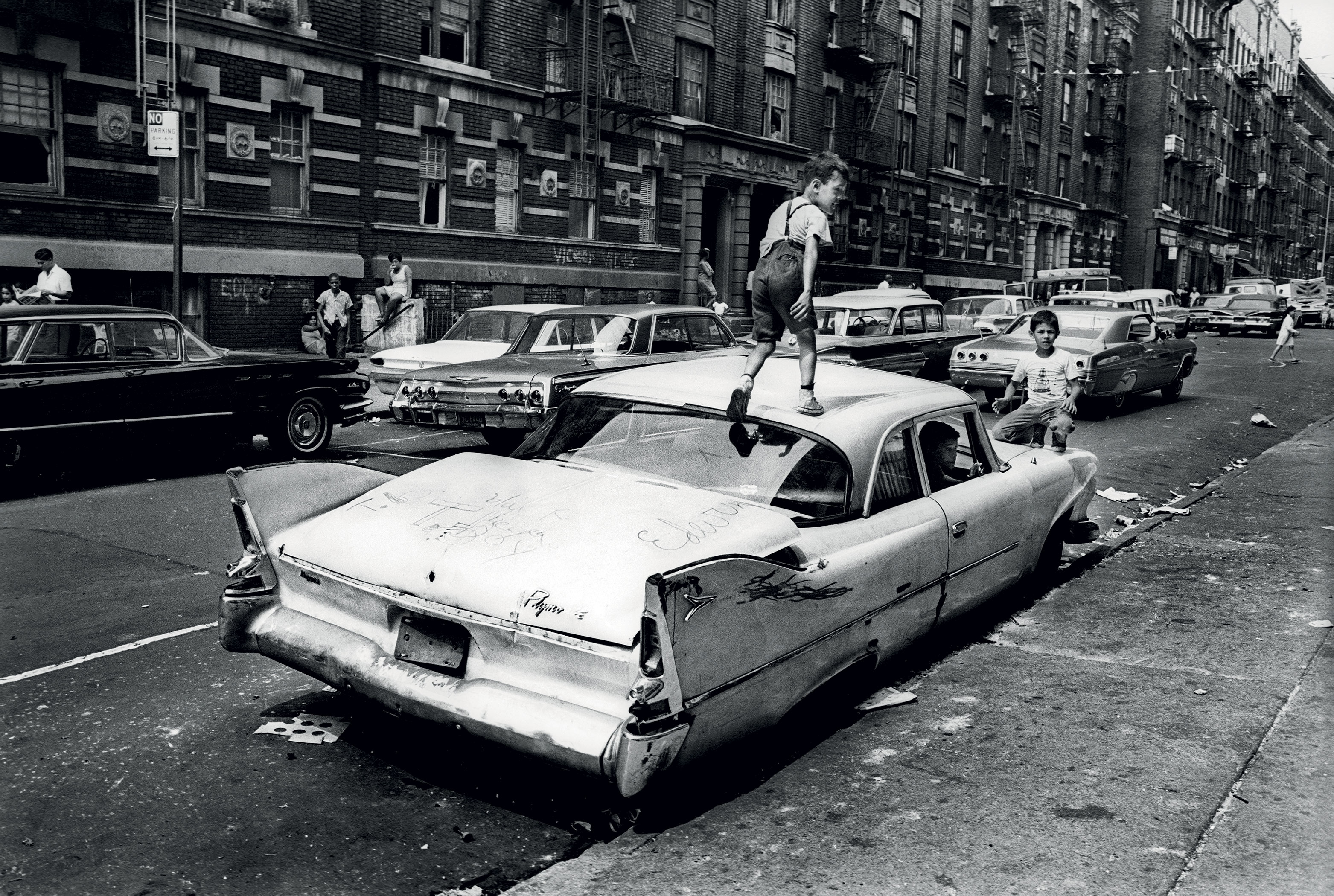 "TRASHED...on Fox Street in the Bronx, an abandoned Plymouth ""Savoy"" becomes a jungle gym for kids to play in and on"