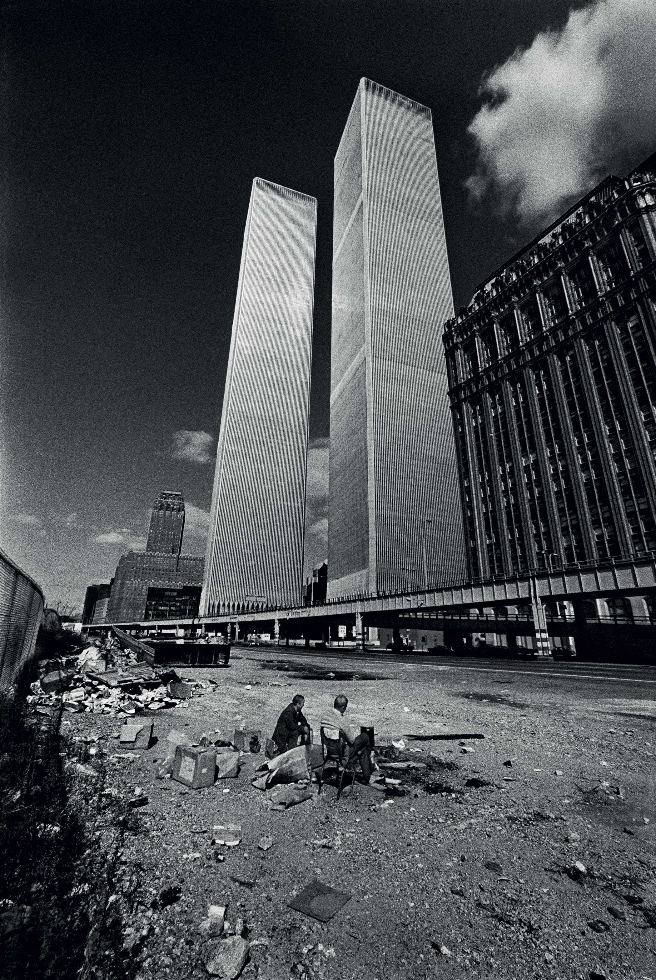 CONTRAST...homeless men squat in the shadow of the recently completed World Trade Center. New York City was on the verge of bankruptcy and the World Trade Center sat largely vacant, unable to find companies to fill its large office spaces in 1975