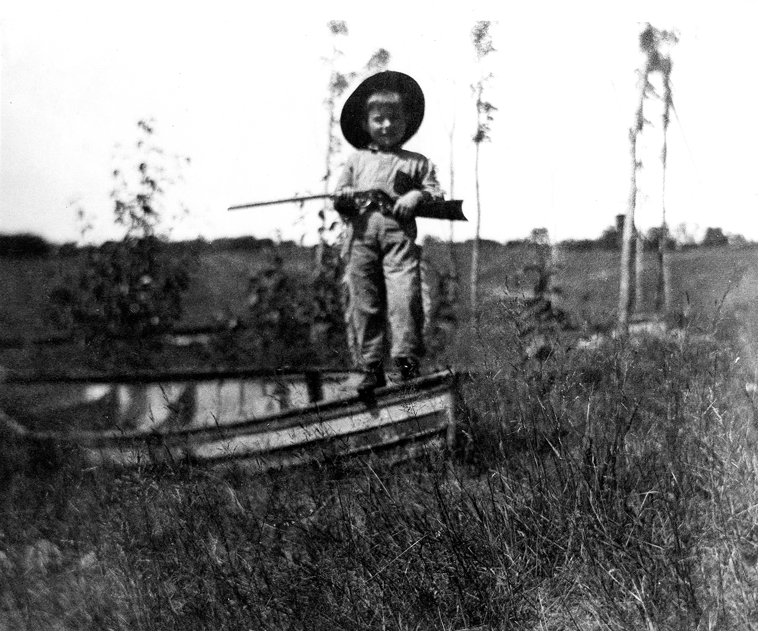 CHILDHOOD...Ernest Hemingway holding a gun at Walloon Lake. Copyright: Public Domain